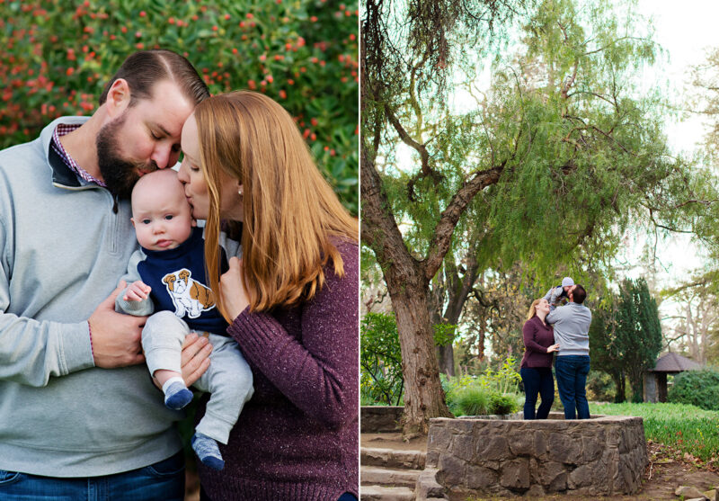 Mom and dad kiss baby boy against tree with red flowers in Davis