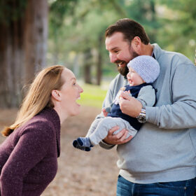 Mom plays peekaboo with baby son as dad holds him in Davis