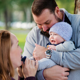 Mom makes baby boy smile as dad holds him outdoors