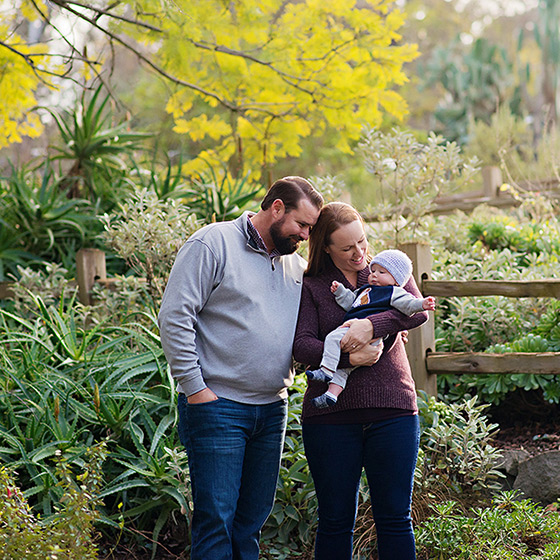 Mom holding baby son while dad smiles at him surrounded by lush greenery in Land Park
