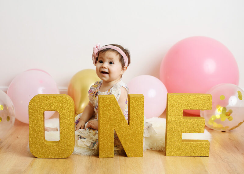 One year old baby girl smiles for camera and poses under ONE letters in Sacramento studio