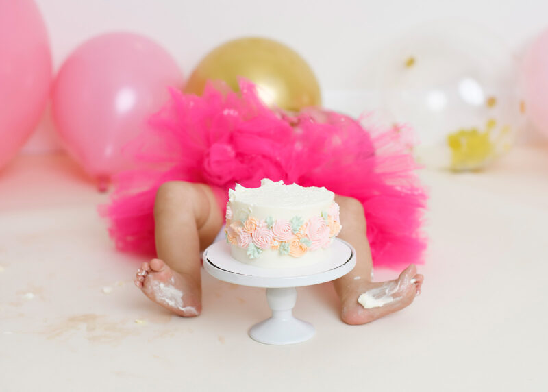 Baby girl falls over with frosting on feet during cake smash in Sacramento studio