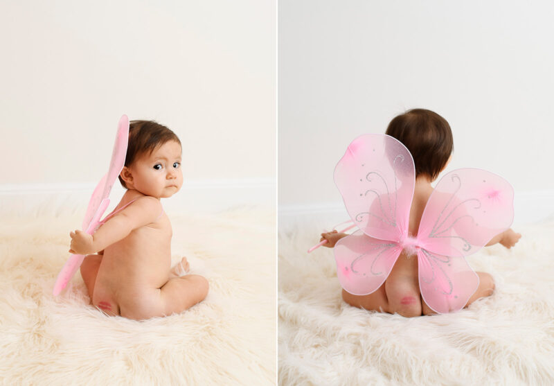 Baby girl in pink fairy wings looks behind her with lipstick kiss on her butt in Sacramento studio