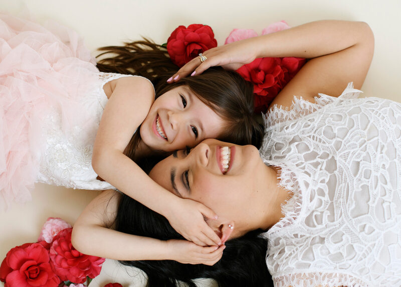 Mom and big sister cuddle close on the floor surrounded by red flowers in Sacramento studio