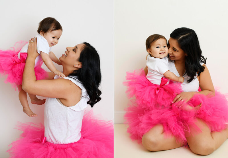 One year old daughter and mom wears pink tutus and smile for the camera in Sacramento studio