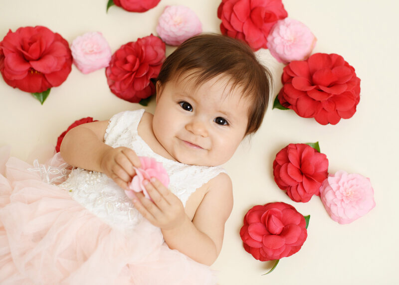 One year old girl lies down surrounded by red and pink flowers in Sacramento studio