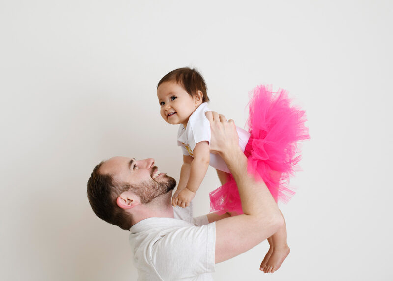 Dad holds one year old daughter up high dressed in pink tutu in Sacramento studio