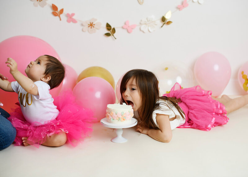 Big sister tries to eat little sister's birthday cake while dressed in pink tutus in Sacramento studio