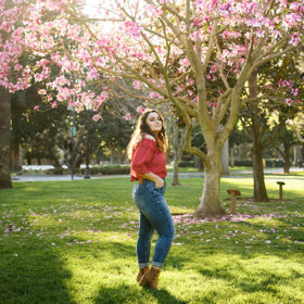 High school senior girl posing under pink blossoms on a tree at Sacramento State Capitol