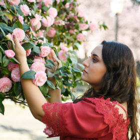 Teen girl admiring pink roses at Sacramento State Capitol