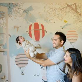 Dad holding newborn baby in nursery with hot air balloon mural Sacramento