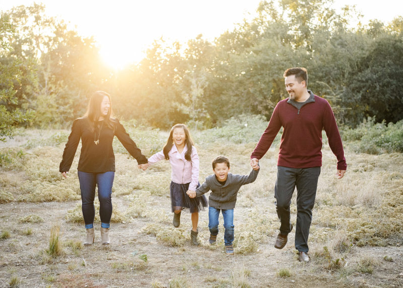 Parents and children holding hands and laughing in dry grass during sunset Sacramento