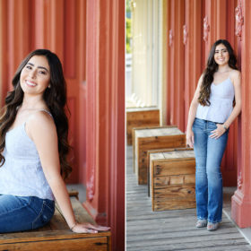 High school senior girl leaning against red wall and crate in Old Town Sacramento