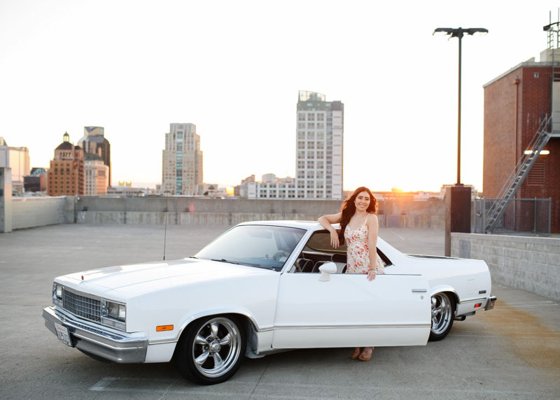 Teen girl posing in white classic car on Sacramento rooftop