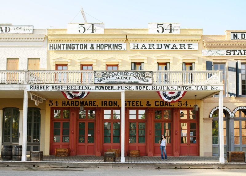 High school graduate posing in front of Huntington and Hopkins Old Sacramento storefront