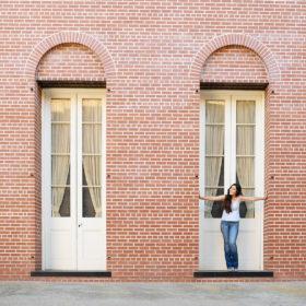 Teen girl standing in front of framed doorway on brick building in Old Sacramento
