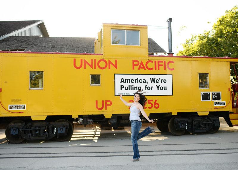 Senior girl skipping through Union Pacific yellow train in Old Sacramento