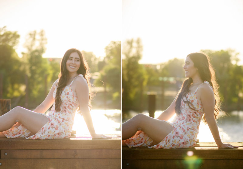 High school senior girl sitting down in front of Sacramento waterfront during golden hour sunset