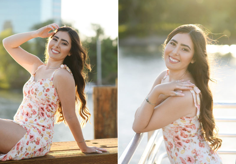 High school senior girl with hand in hair in front of Sacramento waterfront during golden hour sunset