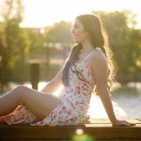 Senior girl posing in front of Sacramento waterfront during sunset wearing long dress golden hour