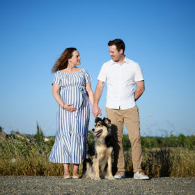 Pregnant woman and husband hold hands and look at each other lovingly with their dog in between them Sacramento