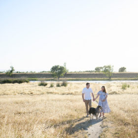 Pregnant woman and husband holding hands and walking through dry grass field with dog in Sacramento