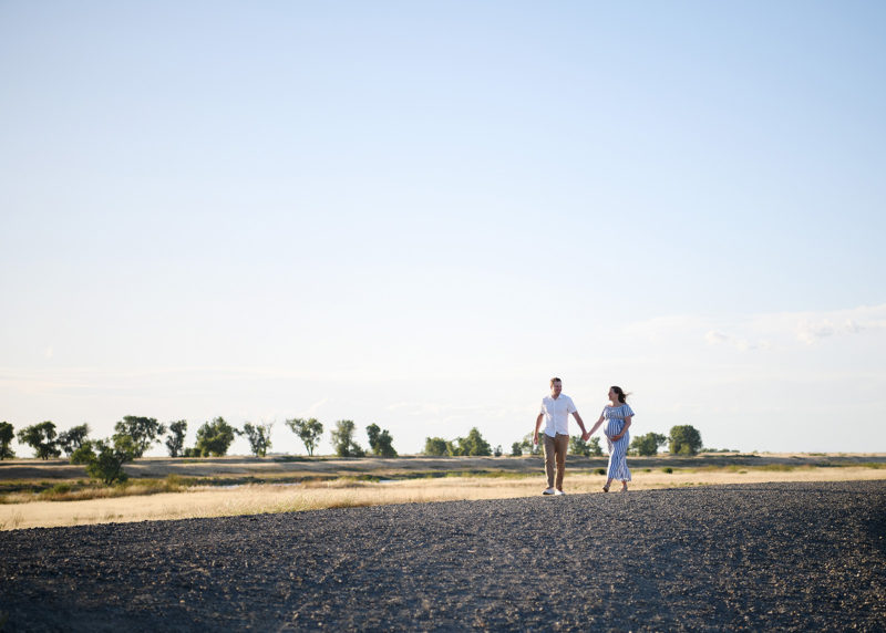Pregnant woman and husband holding hands and walking through dry grass field in Sacramento