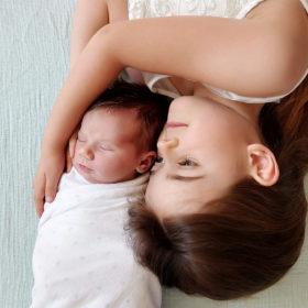 Big sister hugging newborn baby on bed shot with camera phone Sacramento
