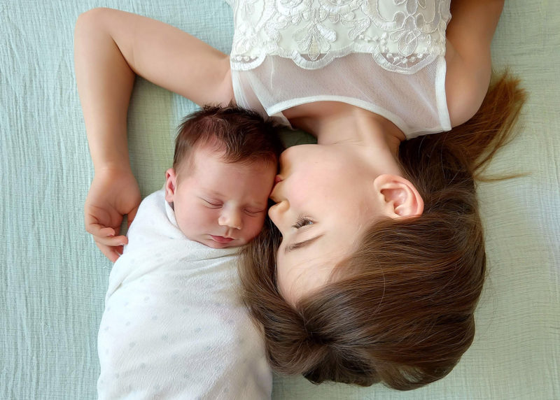 Big sister kissing newborn baby on head while lying on bed shot by camera phone