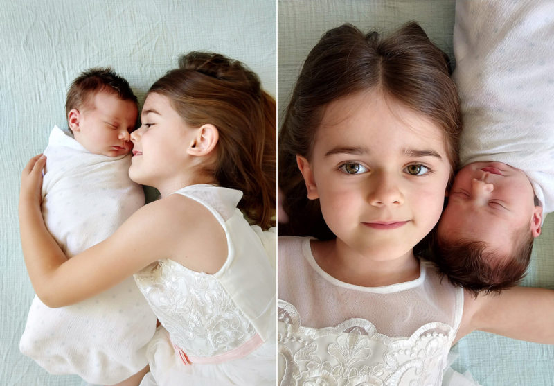 Big sister hugging newborn baby on bed shot by camera phone Sacramento