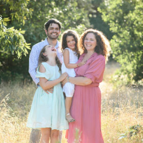 Family laughing and smiling in golden grass with green trees in background Fair Oaks