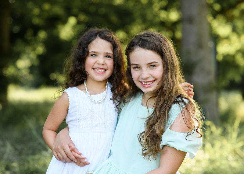 Sisters smiling and hugging in Fair Oaks park Sacramento
