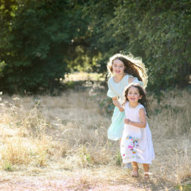 Sisters running through dry grass field in Davis