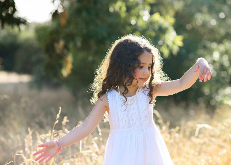Little girl feeling the golden grass with her hands wearing white dress in Davis park
