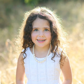 Little girl with wavy hair in the sun smiling for the camera in Davis