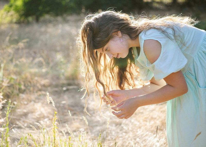 Girl looking at dry grass with long hair in sunshine in Davis