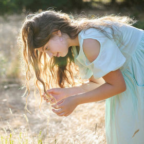 Girl looking at dry grass with long hair in sunshine in Fair Oaks