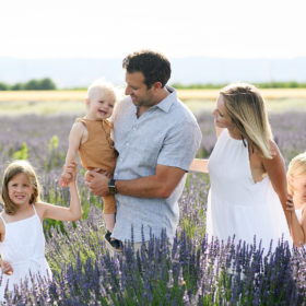 Mom and dad looking at toddler boy while sisters hold hands in the middle of the lavender field in Araceli Farms Dixon