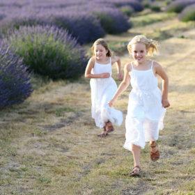 Sisters run along dirt path by lavender field in Araceli Farm Dixon