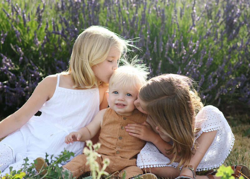 Sisters kiss baby brother on the cheek while sitting on ground in the middle of lavender field in Araceli Farms Dixon