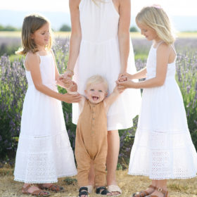 Little girls and mom holding little brother up to stand in Araceli Farms in Dixon