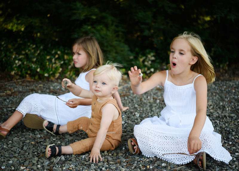 Sisters and brother sitting on rocks and playing with them in Dixon