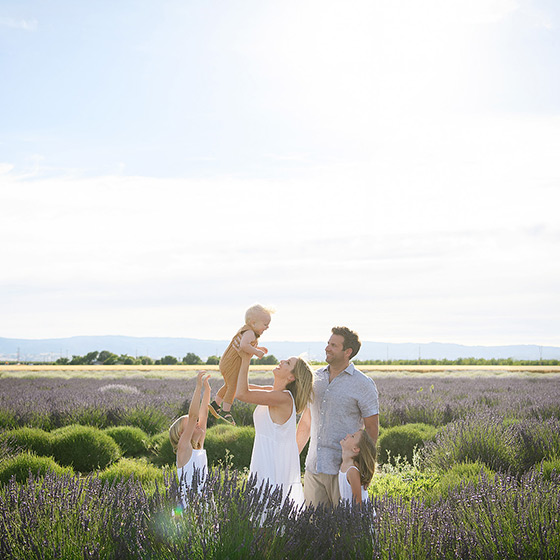 Mom lifting up toddler son while dad and sisters watch in the middle of lavender fields in Dixon Araceli Farms