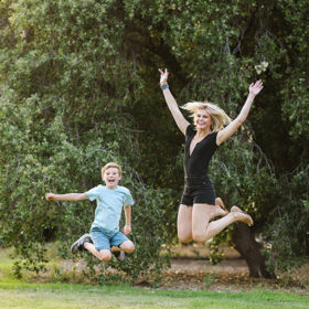 Mom and son jumping in park in Sacramento