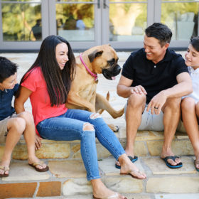 Smiling family looking at their dog while sitting on back porch steps in Sacramento