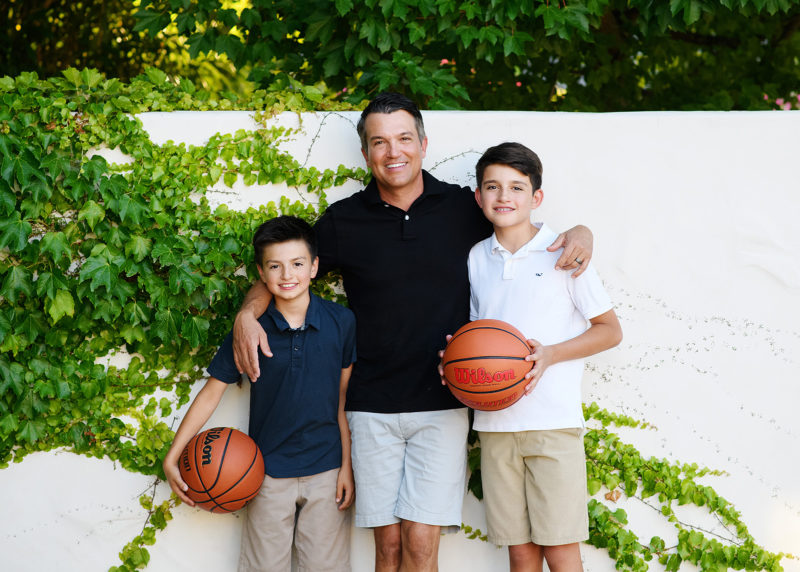 Dad smiling with sons holding basketball outside by creeping ivy in Sacramento home backyard