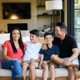 Dad and sons look at mom and smile on the couch in Sacramento home
