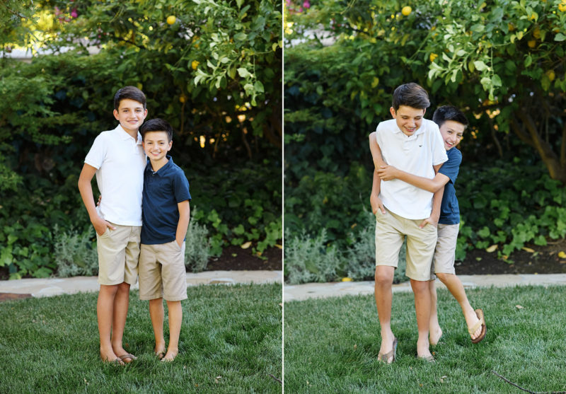 Brothers hug each other and smile in their backyard with lemon tree in Sacramento home
