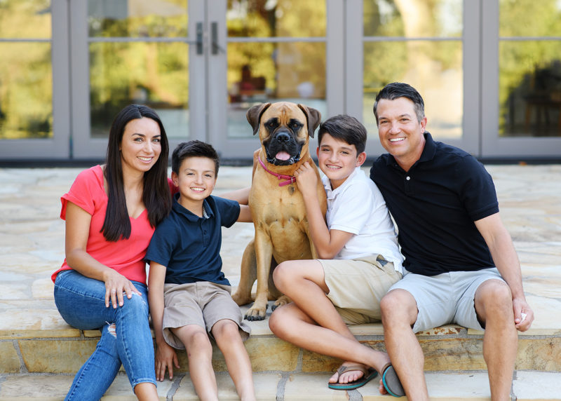 Family poses with their dog sitting on steps of backyard steps in Sacramento home