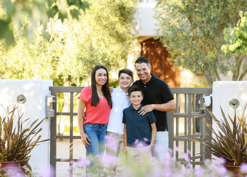 Family smiling framed by large trees and flowers in their backyard home in Sacramento